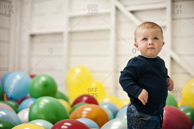 A baby boy surrounded by brightly colored balloons