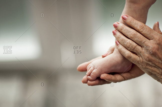A woman cradling a baby's foot