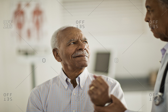 A senior man having his pulse checked by a doctor