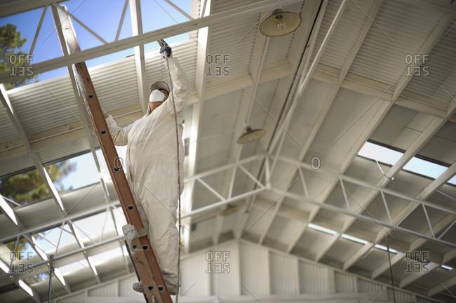 A painter using a spray gun on a roof