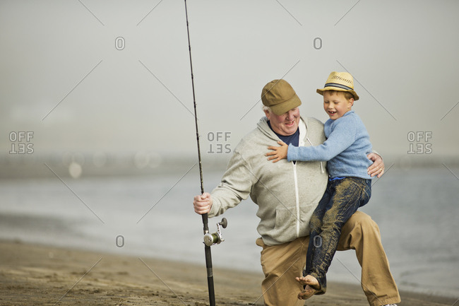 A grandfather and his grandson on the beach during a fishing excursion