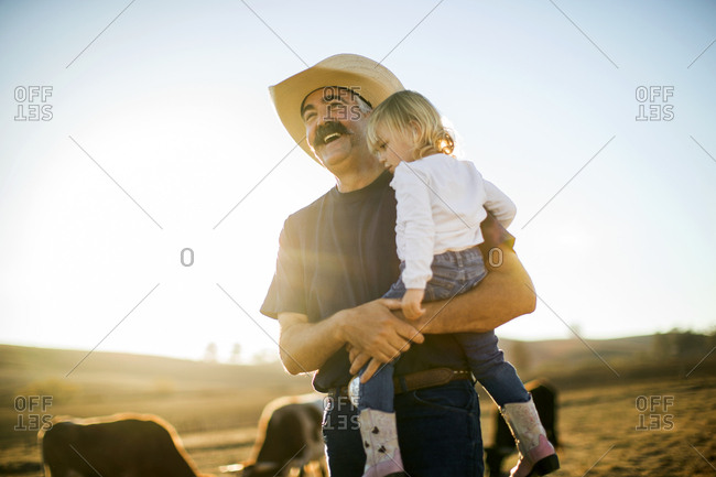 A rancher holding his granddaughter