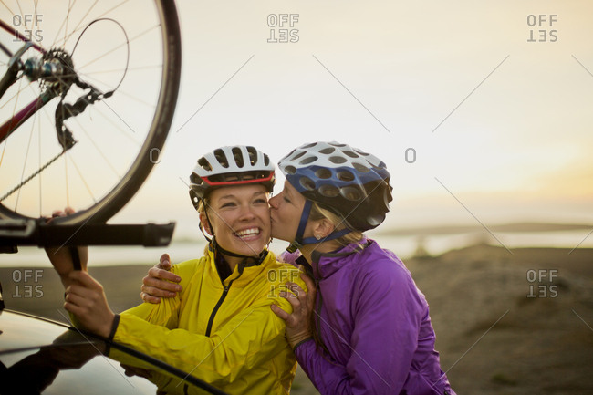 A young woman kissing her friend on the cheek before a bike ride