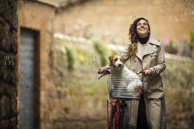 A smiling woman exploring with her dog in her bicycle basket