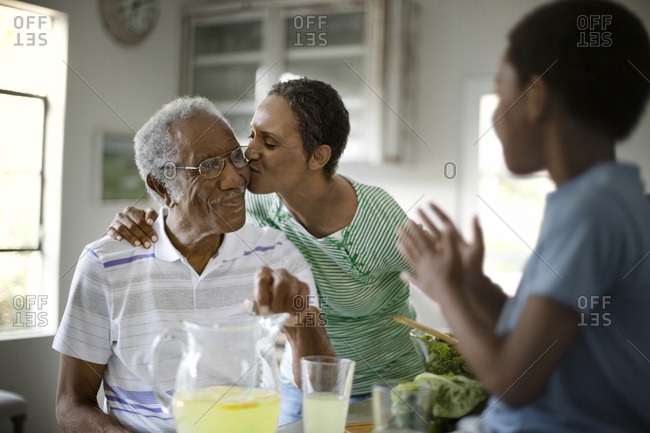 A senior woman kissing her senior father on the cheek, as his grandson looks on clapping