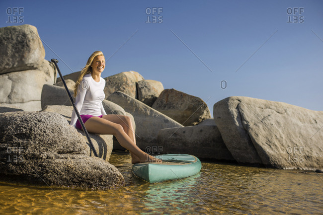 A young woman sitting on a rock while paddle boarding