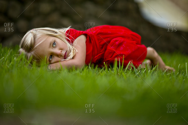 A young girl curled up on the lawn