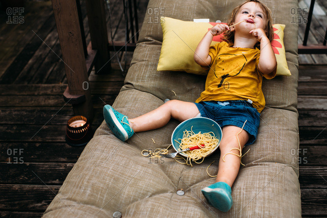 Toddler makes mess while eating spaghetti on a lounge chair