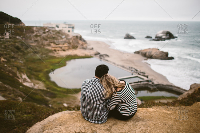 Couple cuddling and overlooking the Sutro Baths
