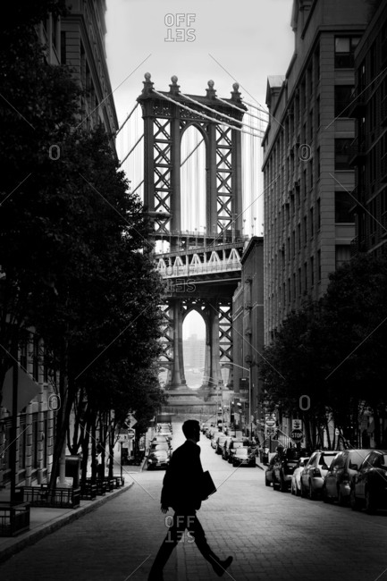 New York City, New York, USA - May 14, 2014: Man walking across the street in Brooklyn with the Manhattan bridge in the background