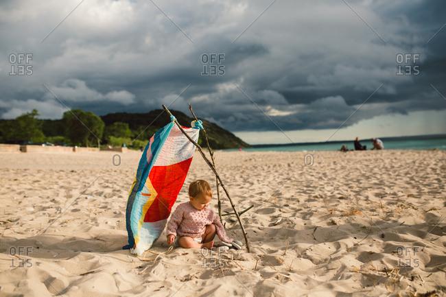 Toddler under makeshift beach structure