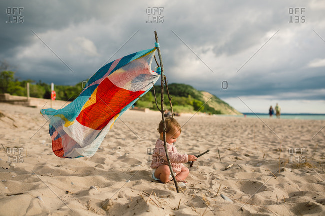 Baby girl sitting with beach stick
