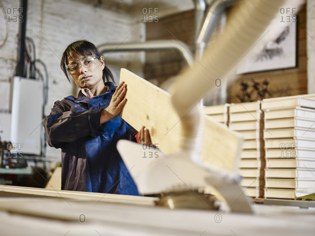Woman examining wood plank in printing workshop