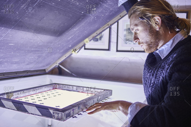 Young man preparing screen on lightbox in traditional print workshop