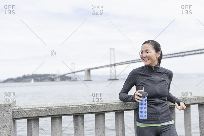 Female runner taking break, Bay Bridge in background, San Francisco, California