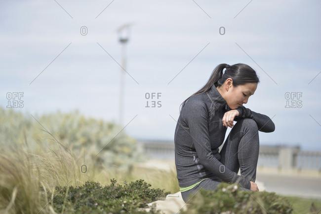 Female runner taking break by roadside, San Francisco, California