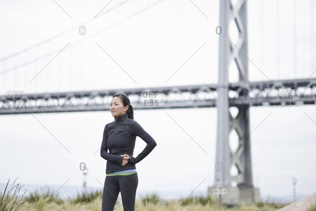 Female runner taking break by bridge, San Francisco, California