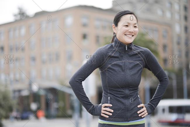 Female runner taking break in city center, San Francisco, California