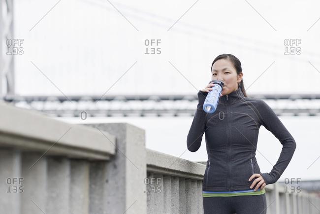 Female runner drinking on bridge, San Francisco, California