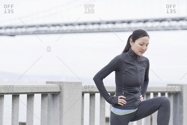 Female runner stretching on bridge, San Francisco, California