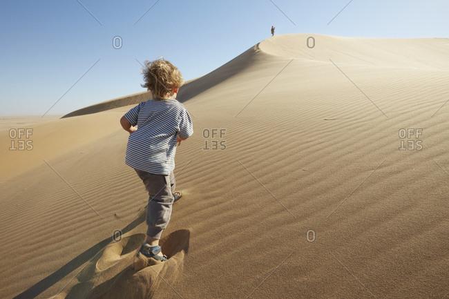 Boy walking on sand, Dune 7, Namib-Naukluft National Park, Africa