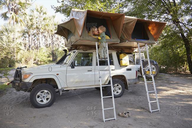 Off road vehicle with sleeping tents above, mother and son bonding, Nata, makgadikgadi, Botswana