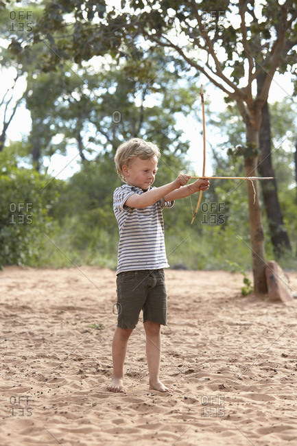 Young boy on sand holding home-made bow and arrow