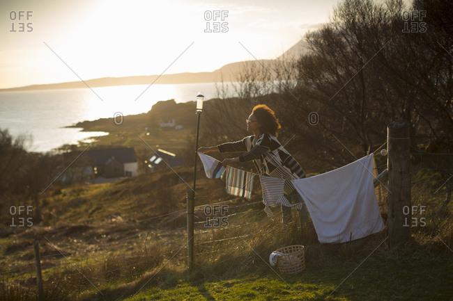 Woman hanging out washing in garden, Tokavaig, Isle of Skye, Scotland