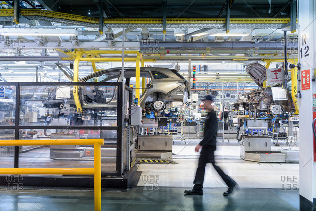 Engineer walking past car production line in car factory