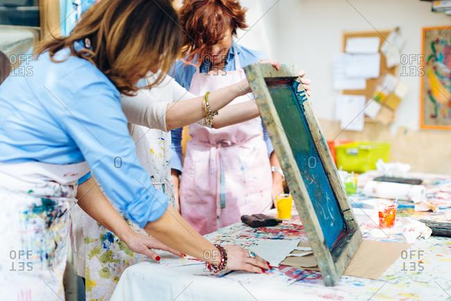 Artist teaching silk screen printing in creative studio