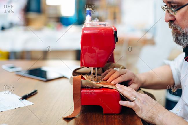 Man using sewing machine in creative studio