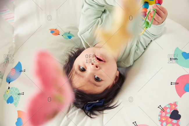 Overhead view of baby girl lying in crib gazing at mobile toy