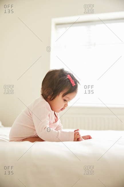 Baby girl sitting up on bed playing with her feet