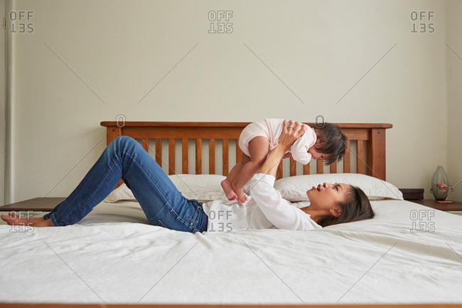 Woman lying on bed holding up baby daughter