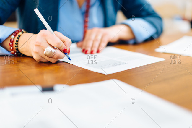 Woman sitting at table, writing on document, mid section, close-up