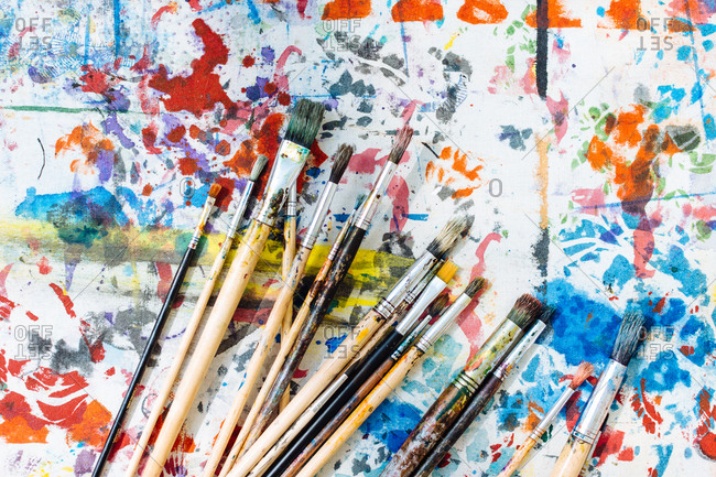 Still life of paintbrushes on colorful painted surface, overhead view