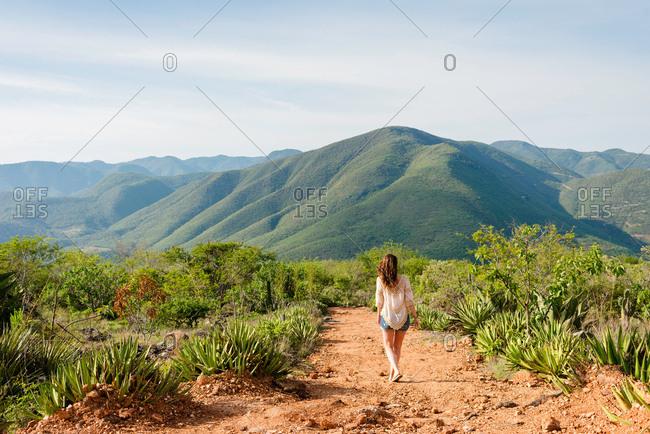 Woman walking along dirt pathway, rear view, Hierve el Agua, Oaxaca, Mexico.