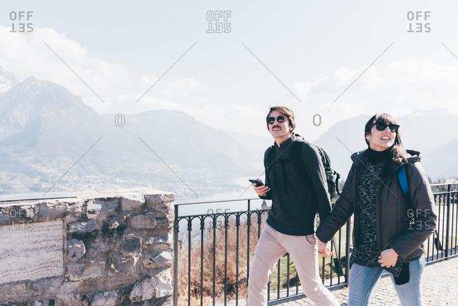 Couple strolling above lakeside, Monte San Primo, Italy