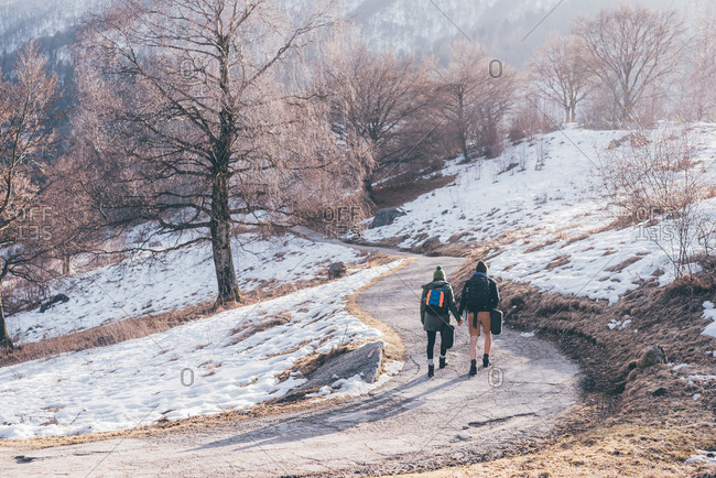 Rear view of hiking couple hiking along snowy rural road, Monte San Primo, Italy