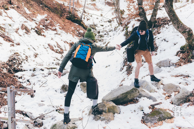 Man hiking in snowy forest giving girlfriend a helping hand, Monte San Primo, Italy