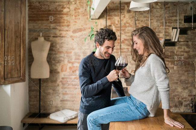 Young couple raising a toast at kitchen counter