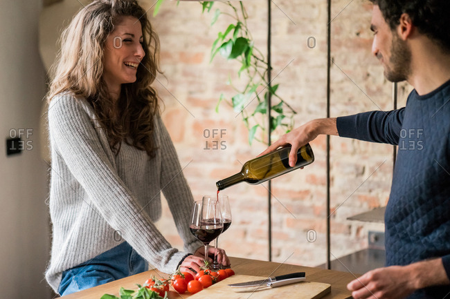 Young couple pouring red wine at kitchen counter