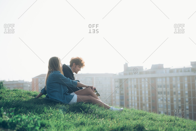 Young couple sitting on grassy verge overlooking rooftops