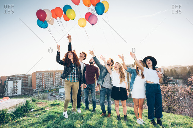 Portrait of group of friends, standing on roof, holding helium balloons