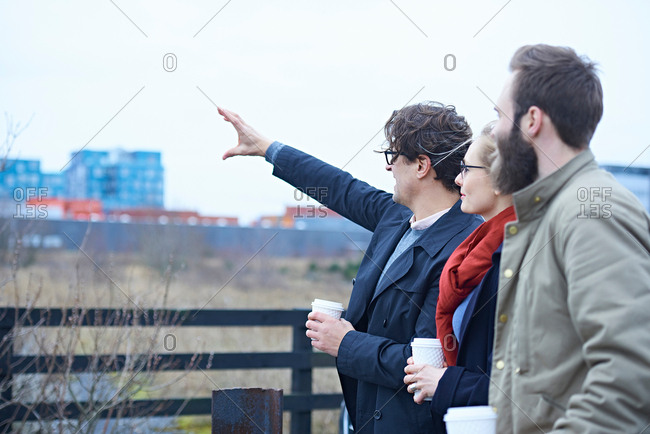 Rear view of design team pointing outside design studio