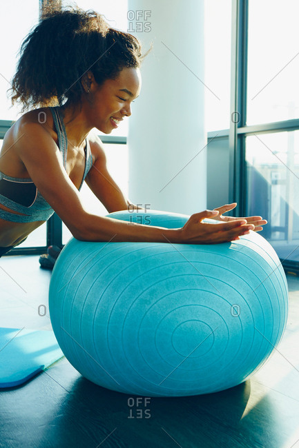 Young woman exercising in gym, using inflatable exercise ball