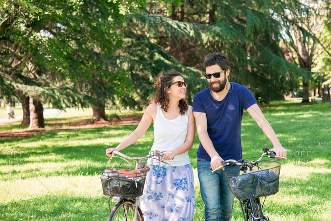 Couple strolling with bicycles in park, Arezzo, Tuscany, Italy