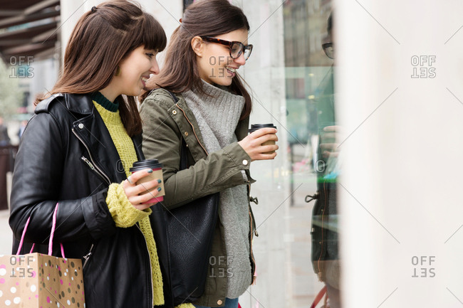 Two young female shoppers with takeaway coffee looking in shop window
