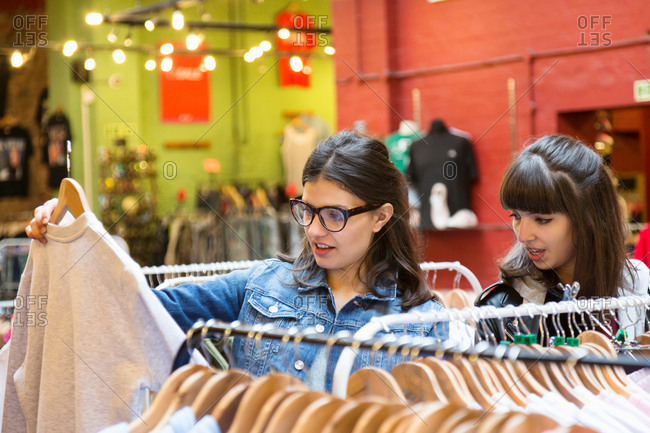Young female shoppers looking at vintage sweatshirt in market hall