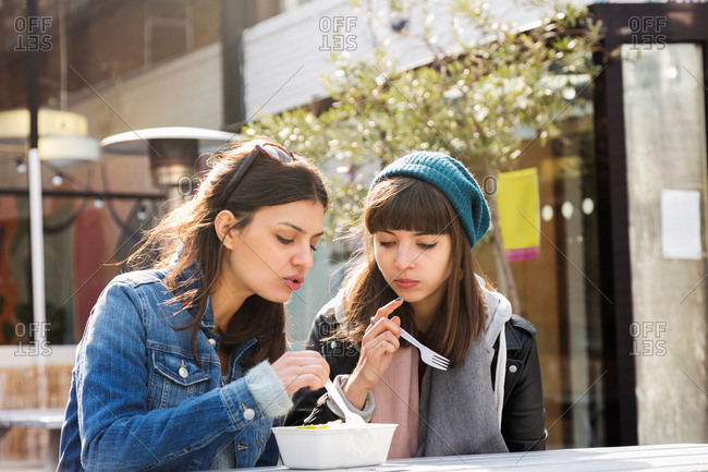 Two young women eating takeaway food at market picnic bench